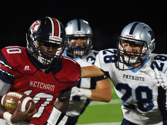 Ketcham's Delvaine Seagers, left, takes the ball down the field as John Jay's Michael Carmosino, right, goes for a tackle during Friday's game.