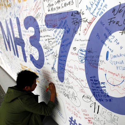 A file picture dated March 13, 2014 shows a passenger writing messages for the passengers of missing Malaysian Airline flight MH370 on a banner at Kuala Lumpur International Airport, Malaysia.