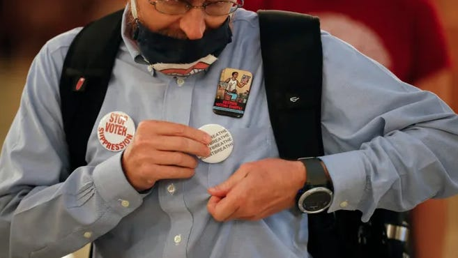 """John Olsen, of Ankeny puts an """"I Can't Breathe"""" button on his shirt during a Black Lives Matter demonstration Monday outside Iowa Gov. Kim Reynolds' office in Des Moines."""