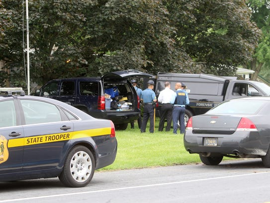 Delaware State Police troopers and the department's Forensics Unit investigate the death of who neighbors say were an elderly couple Tuesday afternoon in the 4000 unit block of Arthursville Road in Hartly.