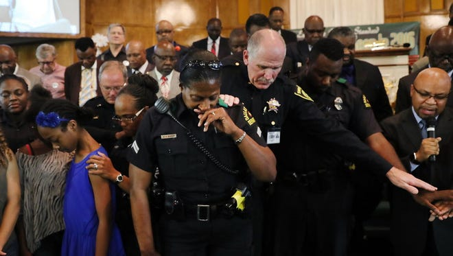 Police officers pray at a vigil in Dallas on July 10, 2016.