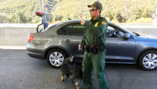In this Thursday, Dec. 14, 2017 photo, a border patrol agent stops a vehicle at a checkpoint in Pine Valley, Calif. California legalizes marijuana for recreational use on Monday, Jan. 1, 2018, but that won't stop federal agents from seizing small amounts on busy freeways and backcountry highways.