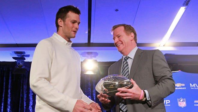 New England Patriots quarterback Tom Brady (left) and NFL Commissioner Roger Goodell pose with the Pete Rozelle trophy during the Super Bowl XLIX-Winning Head Coach and MVP Press Conference at Media Center-Press Conference Room B.