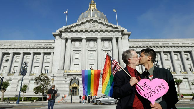 Gay rights advocates John Lewis, left, and his spouse Stuart Gaffney, with the group Marriage Equality USA, kiss across the street from City Hall in San Francisco, Friday, June 26, 2015, following a ruling by the  U.S. Supreme Court that  same-sex couples have the right to marry nationwide. (AP Photo/Jeff Chiu)