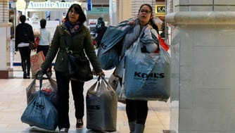 JERSEY CITY, NJ - NOVEMBER 27: Customers carry shopping bags at the Newport Mall during Black Friday Sales on November 27, 2015 in Jersey City, New Jersey.  It was expected that 135.8 million Americans would shop this Black Friday weekend, according to the National Retail Federation .(Photo by Kena Betancur/Getty Images)