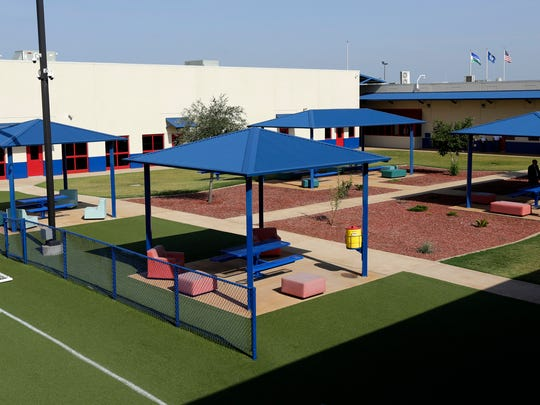 In this July 31, 2014, file photo, a courtyard is seen at the Karnes County Residential Center in Karnes City, Texas. The immigration detention facility has been retooled to house adults with children who have been apprehended at the border.