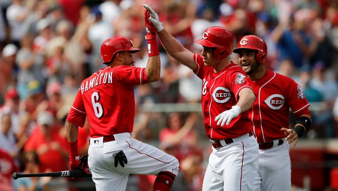 Cincinnati Reds starting pitcher Anthony DeSclafani (28) celebrates with center fielder Billy Hamilton (6) and third baseman Eugenio Suarez (7) after rounding the bases on a grand slam in the third inning of the MLB National League game between the Cincinnati Reds and the Chicago Cubs at Great American Ball Park in downtown Cincinnati on Saturday, June 23, 2018. The Reds led 8-1 after three innings.