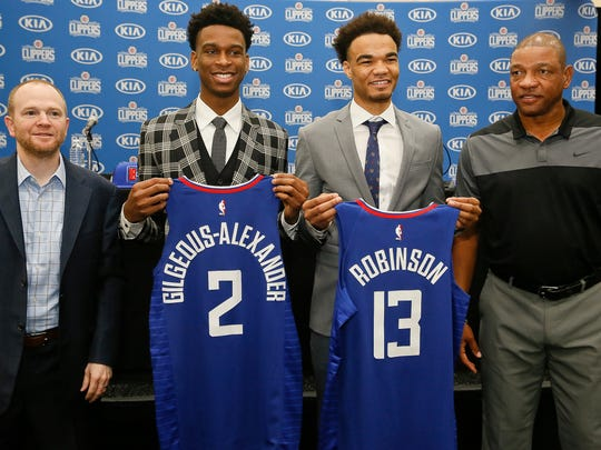 Shai Gilgeous-Alexander, and Jerome Robinson, hold their new team jerseys as they pose for photos with Los Angeles Clippers President of Basketball Operations, Lawrence Frank, far left, and head coach, Doc Rivers, far right, as they are introduced as the newest Clippers guards at the L.A. Clippers Training Center in Los Angeles on Monday, June 25, 2018. (AP Photo/Damian Dovarganes)