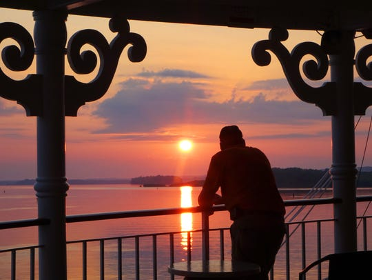 A guest takes in the sunrise from the deck of the American