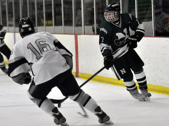 Novi's Alec Wells (7) moves the puck up up the ice on South Lyon Unified's Spencer Stanley (16).