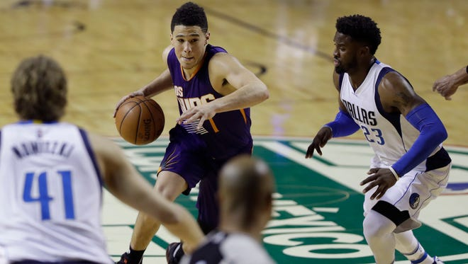 Phoenix Suns Devin Booker drives the ball past Dallas Mavericks Wesley Matthews in the first half of their regular-season NBA basketball game in Mexico City, Thursday, Jan. 12, 2017.