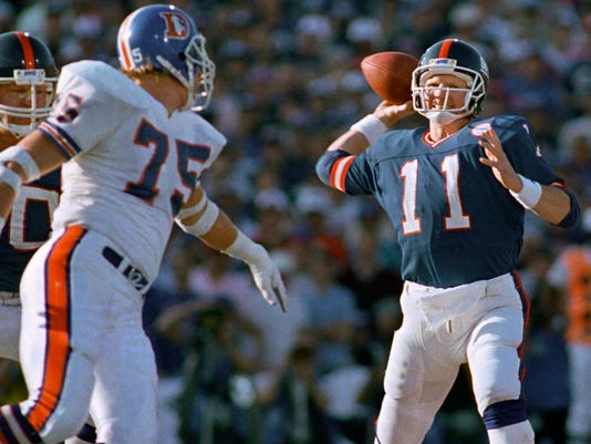 FILE - In this Jan. 25, 1987, file photo, New York Giants quarterback Phil Simms winds up to pass during the first quarter of Super Bowl XXI, against the Denver Broncos in Pasadena, Calif. At left are Denver's Rulon Jones (75) and Giants left tackle Brad Benson (60). Simms completed 22 of 25 for 268 yards, including three touchdown passes, and was unanimously voted the Most Valuable Player. The Giants won 39-20. (AP Photo/Reed Saxon, File)