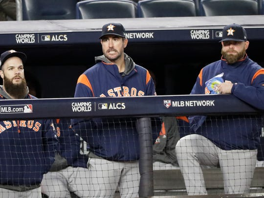Houston Astros' Dallas Keuchel, left, Justin Verlander, center, and Brian McCann watch from the dugout during the ninth inning of Game 3 of baseball's American League Championship Series against the New York Yankees Monday, Oct. 16, 2017, in New York.