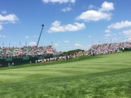 Spectators watch the action around the No. 17 green