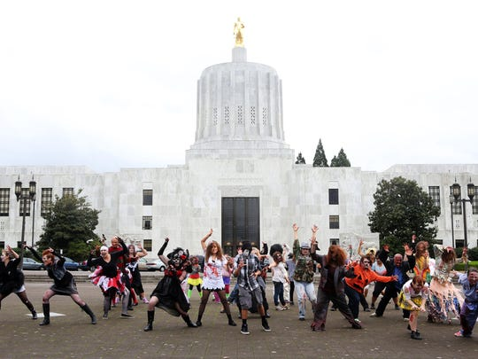 """Dozens of Michael Jackson and/or Halloween enthusiasts dance to his song """"Thriller"""" while bedecked in costume outside the State Capitol."""