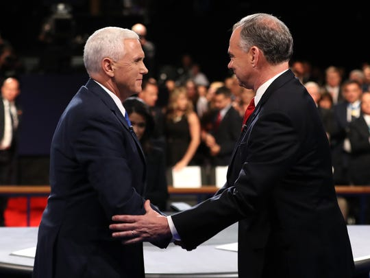 Mike Pence and Tim Kaine shake hands on stage following