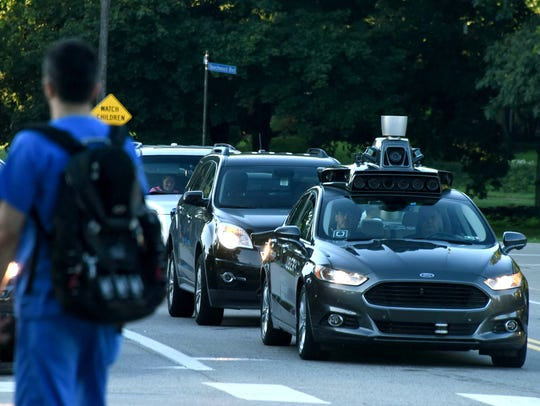 An Uber self-driving Ford Fusion sits at a traffic