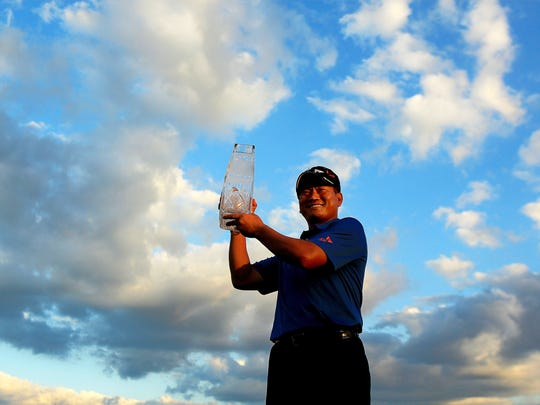 K.J. Choi of South Korea celebrates with the trophy