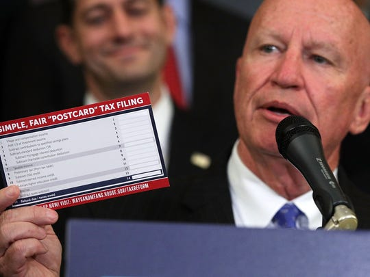 "Rep. Kevin Brady (R-TX) (R) holds up a tax filing ""postcard"""