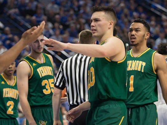 Ernie Duncan talks with teammates during Vermont's