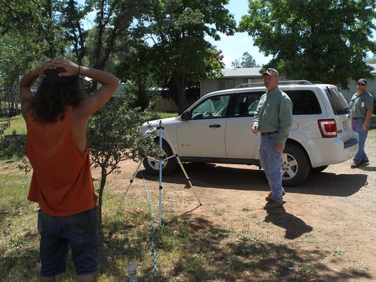 Elias Dippold talks with Shasta County Code Enforcement officers in May 2014 at James Benno's Happy Valley property on Hopekay Lane. Law enforcement and code enforcement agents raided the property where Benno had 101 pot plants, cash and guns. The confiscated the plants and arrested Benno and his two sons.