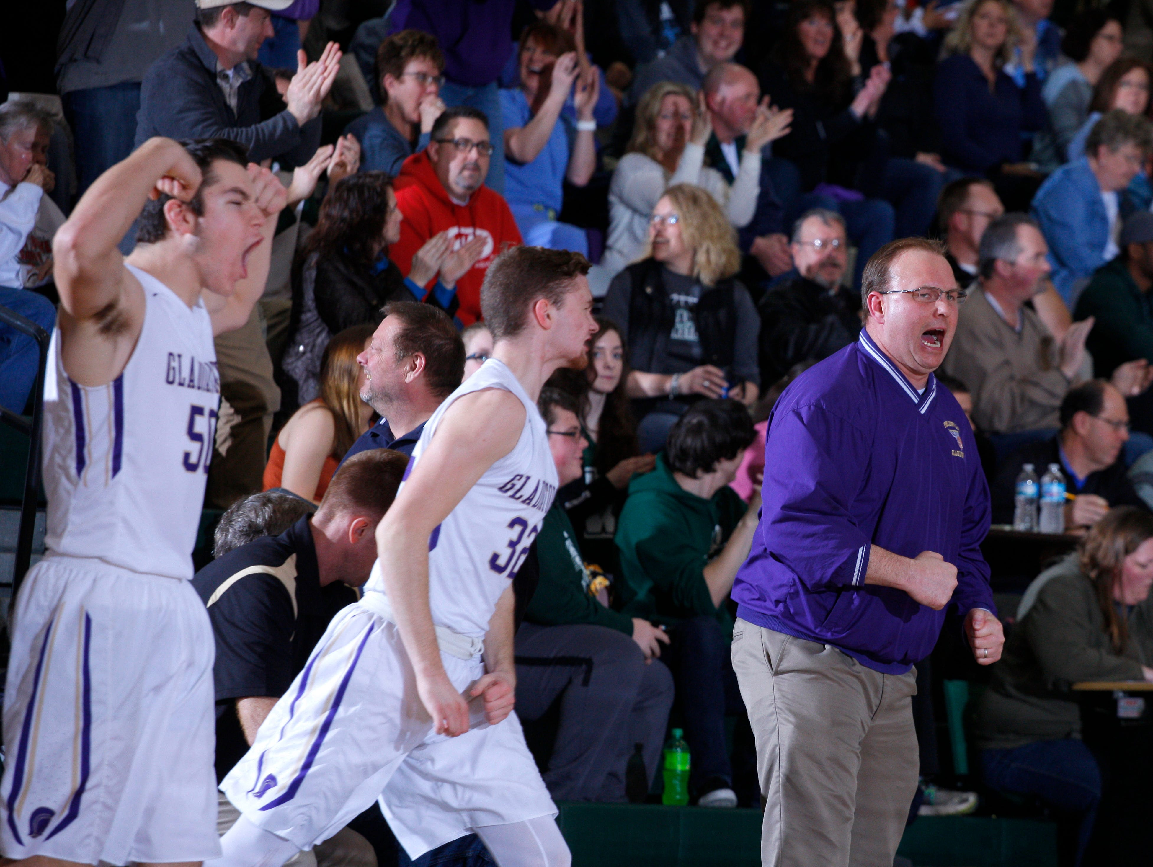 Fowlerville coach Fred Hackett, right, Mitchell Bishop, left, and Caden Collins celebrate during their district game against Lansing Catholic Monday, March 6, 2017, in East Lansing, Mich. Fowlerville won 66-52.