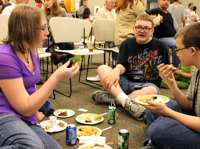 From left:  Morgan Mitchell, 13, Aaron Byrd, 14, and Morgan Clark, 14, all of Erlanger, enjoy food from different countries at the International Food and Flavors event at the Erlanger library.