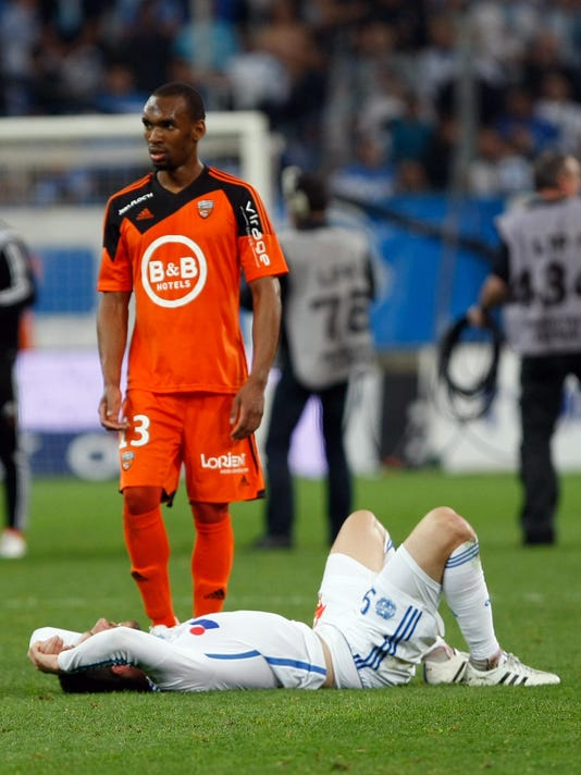 Marseille's French forward Andre-Pierre Gignac, bottom, reacts after Marseille losing against Lorient, during the League One soccer match between Marseille and Lorient, at the Velodrome Stadium, in Marseille, southern France, Friday, April 24, 2015. (AP Photo/Claude Paris)