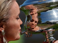 Sofia Kenin of the U.S. holds the Daphne Akhurst Memorial Cup at a photo shoot on the Yarra River following her win over Spain's Garbine Muguruza in women's singles final of the Australian Open tennis championship in Melbourne, Australia, Sunday, Feb. 2, 2020.  (AP Photo/Lee Jin-man)