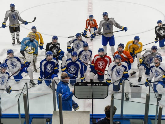 Catherdral players gather around their coaches for instruction during practice Friday, Dec. 15, at the MAC in St. Cloud.