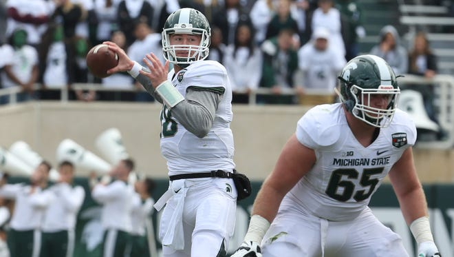 Michigan State quarterback Connor Cook looks for an open man as his offensive lineman Brian Allen gets ready to block during the first half of the Michigan State Spartans annual spring football game at Spartan Stadium in East Lansing, Michigan on Saturday, April 25, 2015. The White team beat the Green team 9-3.
