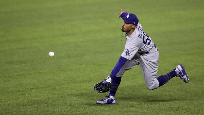 Los Angeles Dodgers right fielder Mookie Betts (50) catches a fly ball from Atlanta Braves shortstop Dansby Swanson then throws to home in the third inning of Game 5 of a baseball National League Championship Series, Friday, Oct. 16, 2020, in Arlington, Texas.