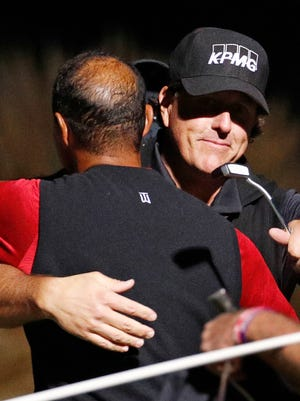 Phil Mickelson hugged Tiger Woods after winning Friday's match in Las Vegas.