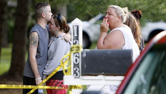 Family members react at the scene where Miami Township police found a couple dead inside of their home after a domestic dispute was called in on Sunday evening after a domestic dispute.