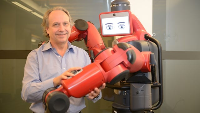 Rethink Robotics founder Rodney Brooks and his latest creation, Baxter, a $25,000 robot built for manufacturing work.
