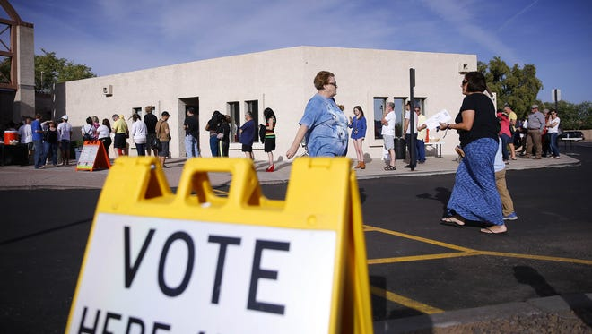 People wait in line to vote in Arizona's presidential preference election at Mountain View Lutheran Church in Phoenix.