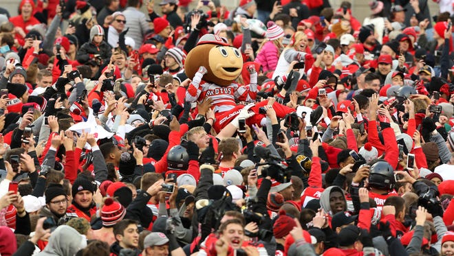Brutus Buckeye crowd surfs as fans surge onto the field following the win over Michigan at Ohio Stadium. Ohio State won 30-27.
