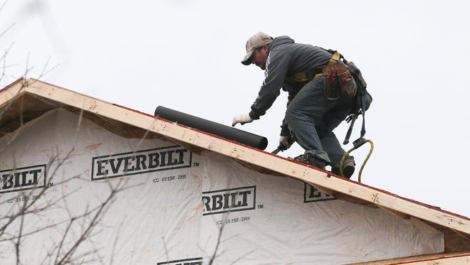 A man installs a roof on a new home under construction in Atlanta.