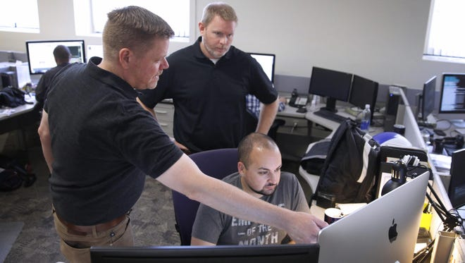 Members of the Gannett Innovation Lab team work together at the Democrat and Chronicle. They are from left, Kevin Poortinga, vice president/innovation lab, Tim Carlson, innovation development director and Michael Vargas-Rodriguez, designer.