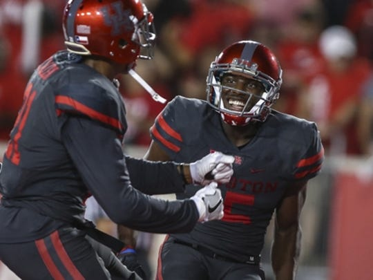 Houston's Linell Bonner (15) smiles after scoring a touchdown against UConn