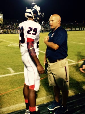 Creek Wood High's Quinton Poole checks in with assistant coach Robby Street after Poole's 21-yard TD run.