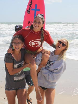 Coral Schuster being carried to the beach after winning the U-14 and scoring a 9.4 on a single wave.