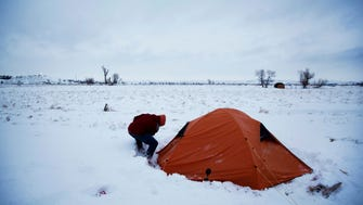 """In this Wednesday, Nov. 30, 2016 photo, Roy Tom of Ontario, Canada, and a member of the Ojibwa Native American tribe clears away snow from his tent where he's lived for over two months at the Oceti Sakowin camp where people have gathered to protest the Dakota Access oil pipeline, in Cannon Ball, N.D. """"You have to get used to it,"""" Tom said of the snow and cold weather."""