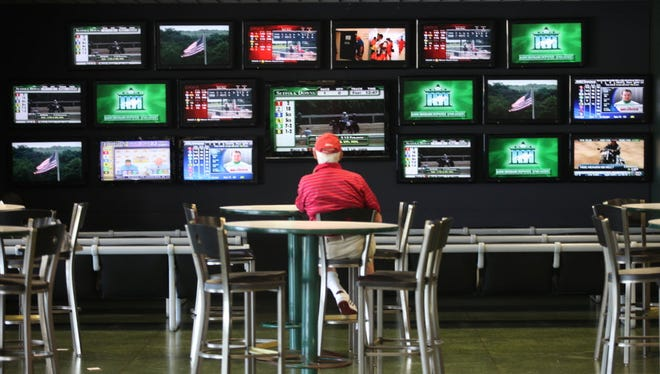 Horse-racing monitors at Monmouth Park in Oceanport, where bettors will soon be able to wager on professional sports games.