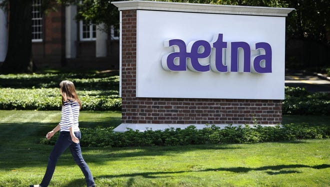 File photo taken in 2016 shows a woman walking  past a sign for healthcare insurance giant Aetna at the company current headquarters in Hartford, Conn.