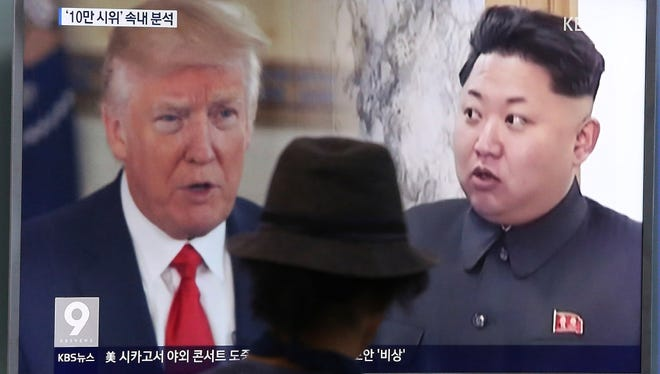 A man watches a television screen showing President Donald Trump, left, and North Korean leader Kim Jong-un during a news program at the Seoul Train Station in Seoul, South Korea.