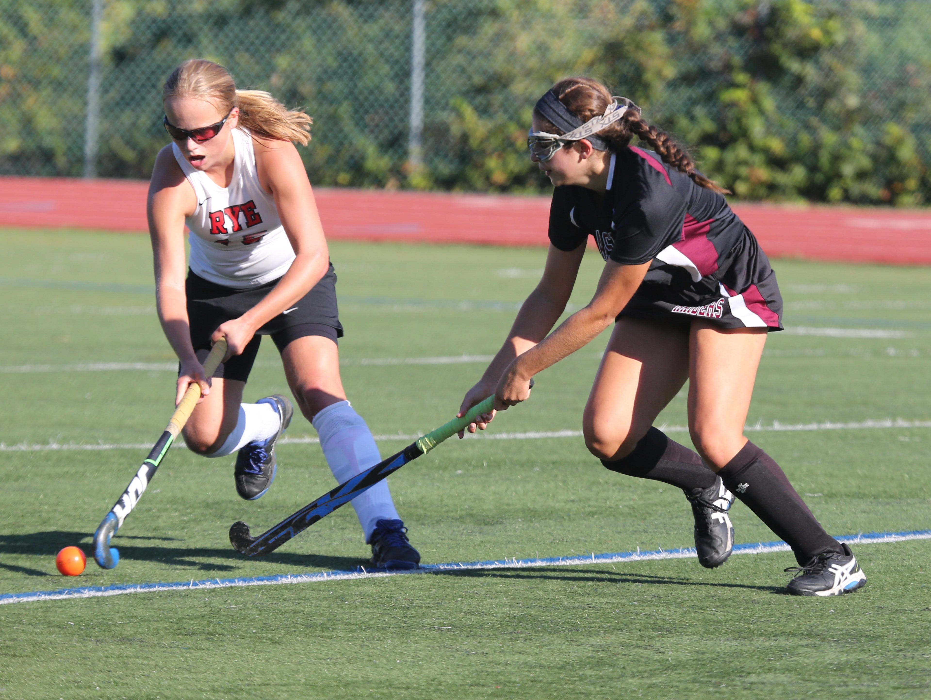 Rye's Fusine Govaert moves the ball in front of Scarsdale's Ali Bauersfeld during their field hockey game in Rye, Sept. 24, 2015. Rye beat Scarsdale, 3-1.