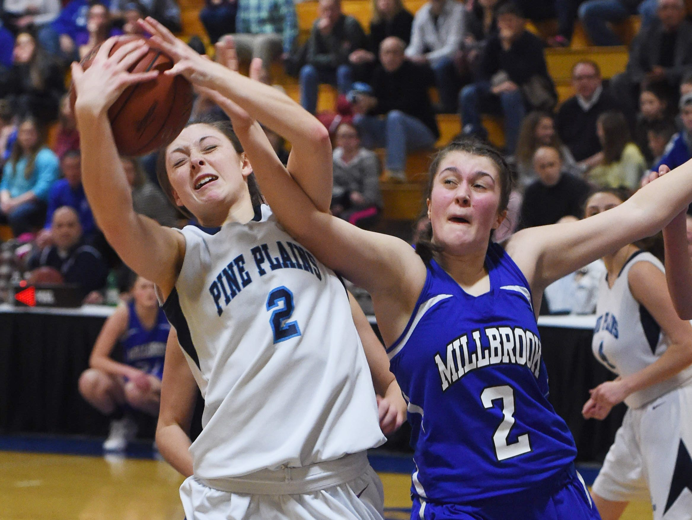 Pine Plains' Haley Strang, left, wretches a rebound away from Millbrook's Hannah Fisher, right, during Friday's Section 9 championship game at Mount Saint Mary College in Newburgh.
