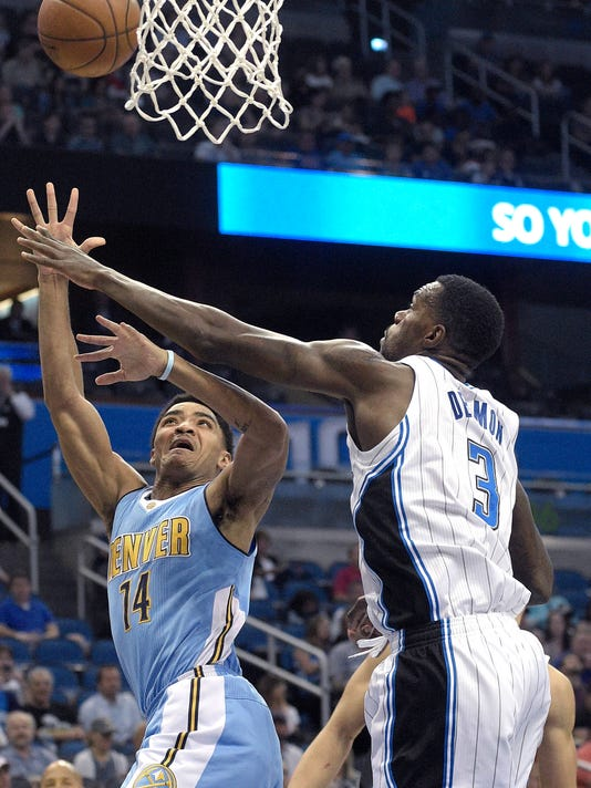 Denver Nuggets guard Gary Harris (14) goes up for a shot in front of Orlando Magic center Dewayne Dedmon (3) during the first half of an NBA basketball game in Orlando, Fla., Tuesday, March 15, 2016. (AP Photo/Phelan M. Ebenhack)