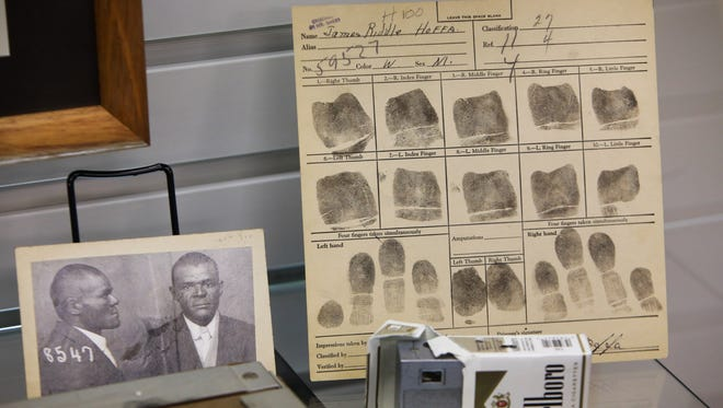 Booking fingerprints for James Riddle Hoffa sit on display at the Detroit Police Museum, along with a pack of Marlboros that hides a camera.
